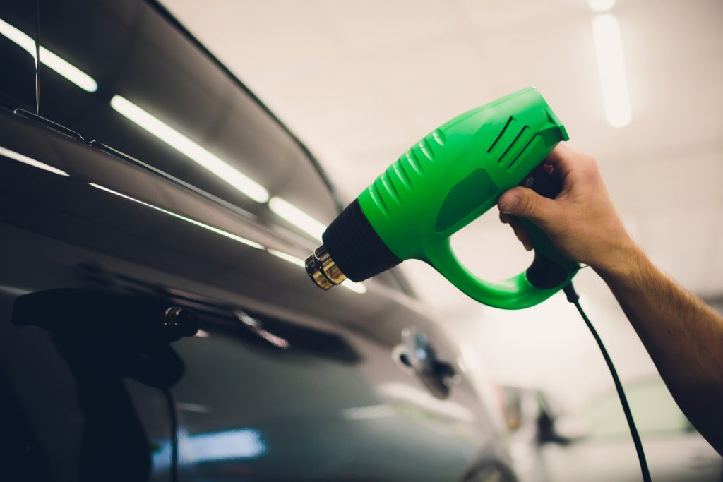 Master installs tint film for car with hairdryer. Concept protection car