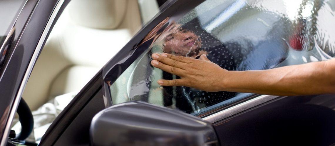 Man installing window tinting on car.